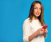 Muchacha sonriente hermosa con el teléfono móvil Imagenes de archivo