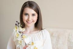 Muchacha sonriente hermosa con la flor de la orquídea imágenes de archivo libres de regalías