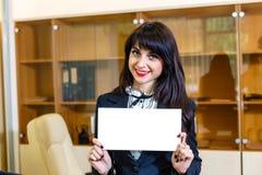 Muchacha sonriente hermosa con la tarjeta vacía en oficina Fotos de archivo libres de regalías