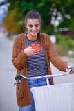 Muchacha sonriente hermosa con una bicicleta en el camino Imágenes de archivo libres de regalías