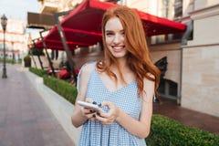Muchacha sonriente hermosa del pelirrojo con el pelo largo usando el teléfono móvil Foto de archivo libre de regalías