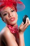 Muchacha sonriente hermosa del pinup que controla maquillaje Fotos de archivo libres de regalías