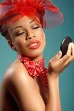 Muchacha sonriente hermosa del pinup que controla maquillaje Imagenes de archivo