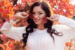 Muchacha sonriente hermosa en hojas de otoño coloridas Imagenes de archivo