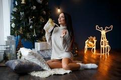 Muchacha sonriente hermosa en un jersey blanco cerca del árbol de los chrismas Fotos de archivo libres de regalías