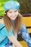 Muchacha sonriente hermosa en un sombrero azul con los auriculares rosados que se sientan en el parque en un banco y que escuchan Imagenes de archivo