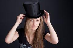 Muchacha sonriente hermosa en un sombrero negro Fotografía de archivo