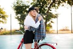Muchacha sonriente hermosa joven con el pelo rubio alegre que mira a un lado mientras que abraza al muchacho en la bicicleta roja Imagen de archivo libre de regalías