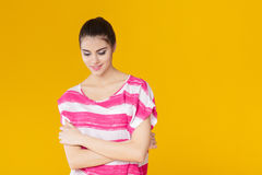 Muchacha sonriente hermosa joven en camisa rosada en fondo amarillo Fotos de archivo libres de regalías