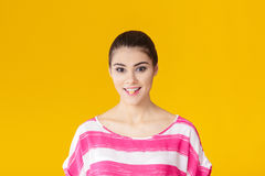 Muchacha sonriente hermosa joven en camisa rosada en fondo amarillo Imagenes de archivo