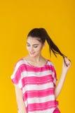 Muchacha sonriente hermosa joven en camisa rosada en fondo amarillo Foto de archivo libre de regalías