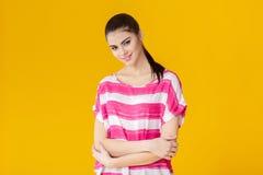 Muchacha sonriente hermosa joven en camisa rosada en fondo amarillo Foto de archivo