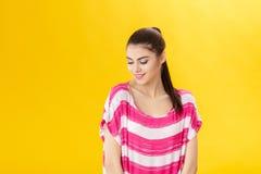 Muchacha sonriente hermosa joven en camisa rosada en fondo amarillo Fotos de archivo