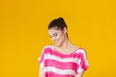 Muchacha sonriente hermosa joven en camisa rosada en fondo amarillo Imagen de archivo libre de regalías