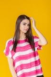 Muchacha sonriente hermosa joven en camisa rosada en fondo amarillo Imagen de archivo