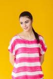 Muchacha sonriente hermosa joven en camisa rosada en fondo amarillo Fotografía de archivo libre de regalías