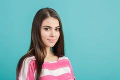 Muchacha sonriente hermosa joven en camisa rosada en fondo azul Foto de archivo libre de regalías