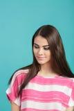 Muchacha sonriente hermosa joven en camisa rosada en fondo azul Foto de archivo