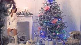 Muchacha sonriente hermosa joven en un suéter hecho punto sobre su baile desnudo del cuerpo y canto cerca del árbol de navidad metrajes