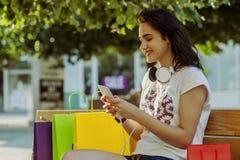 Muchacha sonriente hermosa joven que descansa sobre el banco después de hacer compras Imagen de archivo