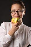 Muchacha sonriente hermosa que come la manzana verde Imagenes de archivo