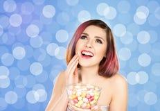 Muchacha sonriente hermosa que come los dulces Imagenes de archivo