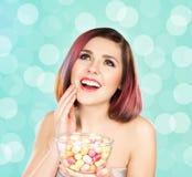 Muchacha sonriente hermosa que come los dulces de un cuenco Fotos de archivo libres de regalías