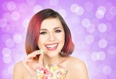 Muchacha sonriente hermosa que come los dulces de un cuenco en fondo de la burbuja Imagenes de archivo