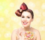 Muchacha sonriente hermosa que come los dulces de un cuenco en fondo del centelleo Fotografía de archivo libre de regalías