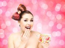 Muchacha sonriente hermosa que come los dulces de un cuenco en fondo del centelleo Imágenes de archivo libres de regalías