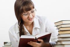 Muchacha sonriente hermosa que lee cuidadosamente un libro Imagen de archivo