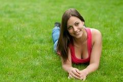 Muchacha sonriente hermosa que miente en la hierba Fotos de archivo