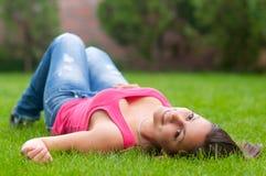 Muchacha sonriente hermosa que miente en la hierba Imagen de archivo libre de regalías