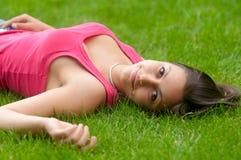 Muchacha sonriente hermosa que miente en la hierba Foto de archivo