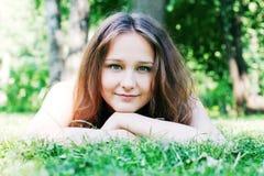 Muchacha que miente en la hierba en un parque Imagen de archivo libre de regalías