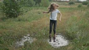 Muchacha sonriente hermosa que salta en charco muy fangoso en la carretera nacional almacen de video