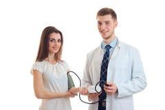Muchacha sonriente hermosa que se coloca al lado de un doctor que le toma la presión Imágenes de archivo libres de regalías