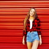 Muchacha sonriente hermosa que se coloca cerca de la pared roja - copie el espacio Foto de archivo libre de regalías
