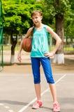 Muchacha sonriente hermosa que se coloca con un baloncesto en cancha de básquet al aire libre Foto de archivo