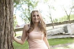 Muchacha sonriente hermosa que se coloca durante verano verde Imagen de archivo