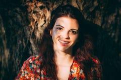 Muchacha sonriente hermosa que se inclina en árbol Fotografía de archivo