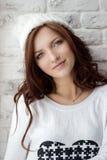 Muchacha sonriente hermosa que se sienta cerca de la ventana en casquillo blanco caliente Imagen de archivo