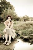 Muchacha sonriente hermosa que se sienta cerca del río Fotografía de archivo libre de regalías