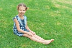 Muchacha sonriente hermosa que se sienta en hierba verde Imagen de archivo