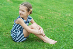 Muchacha sonriente hermosa que se sienta en hierba verde Fotografía de archivo libre de regalías