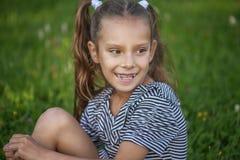 Muchacha sonriente hermosa que se sienta en hierba verde Fotos de archivo