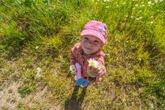 Muchacha sonriente hermosa que sostiene la flor Fotos de archivo