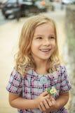 Muchacha sonriente hermosa que sostiene la flor Imagenes de archivo