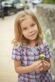 Muchacha sonriente hermosa que sostiene la flor Imagen de archivo