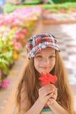 Muchacha sonriente hermosa que sostiene la flor roja Fotos de archivo libres de regalías